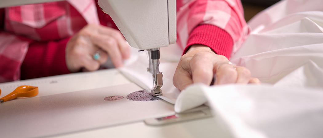 Person sewing cushion covers with a sewing machine
